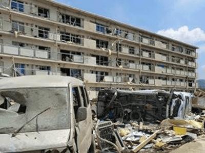 被害を受けた住宅と大破した自動車